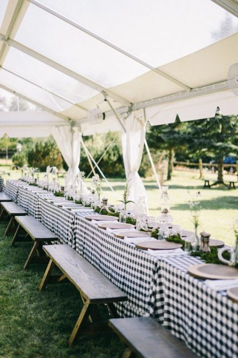 a simple rustic rehearsal dinner tablescape with a checked tablecloth, greenery, some blooms and lanterns