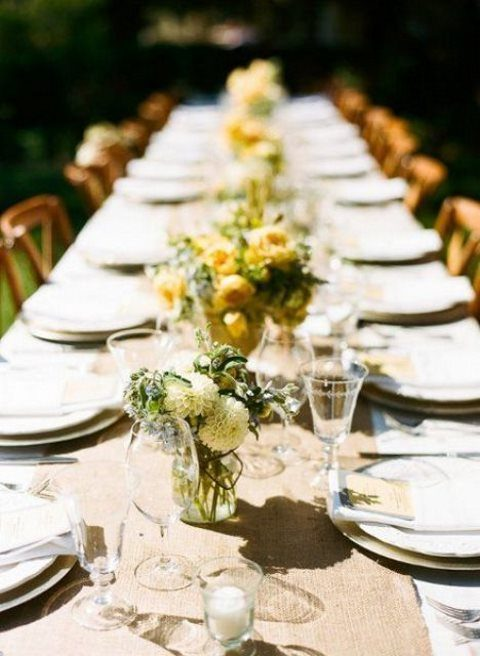 a simple rustic table setting with a white tablecloth, a burlap runner, yellow and white blooms for centerpieces
