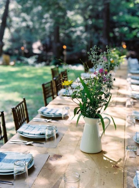 a simple rustic tablescape with an uncovered table, wildflower arrangements in jugs, checked napkins and simple placemats