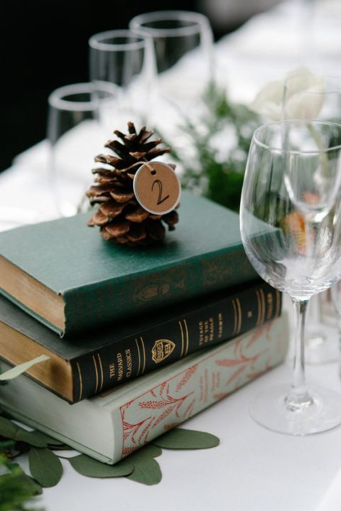a simple wedding centerpiece with a stack of books, greenery and a pinecone with a tag on top
