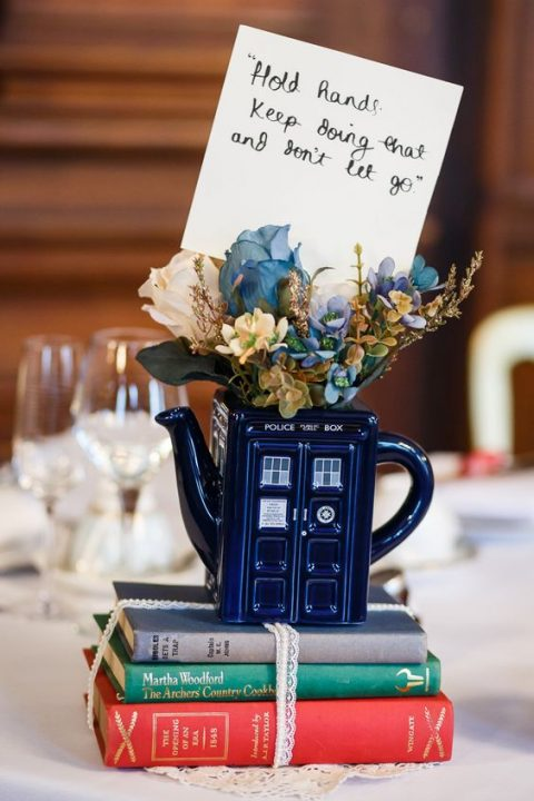 a stack of books, a Doctor Who themed vase with blue and white blooms