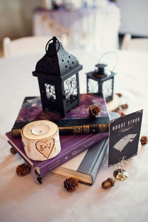 a stack of books, a birch candle holder, pinecones and acorns, black lanterns and a table name