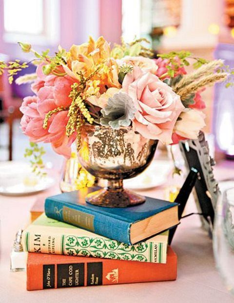 a stack of books, a large metallic bowl with peonies, roses and dried herbs
