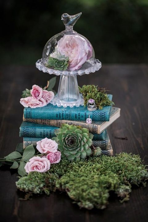 a stack of books, succulents, pink roses, moss and a bloom in a tiny cloche