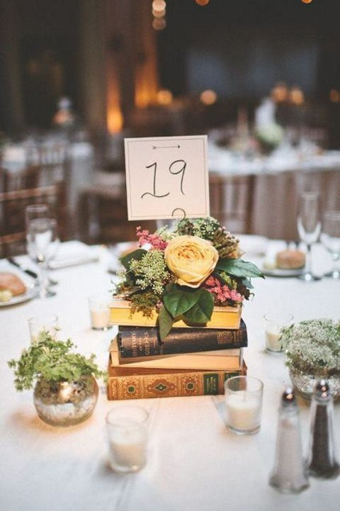 a stylish centerpiece with a stack of books, lush greenery and blooms and a table number on top
