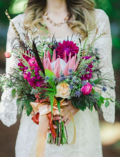 a super bright wedding bouquet with fuchsia blooms, a king protea, feathers and greenery