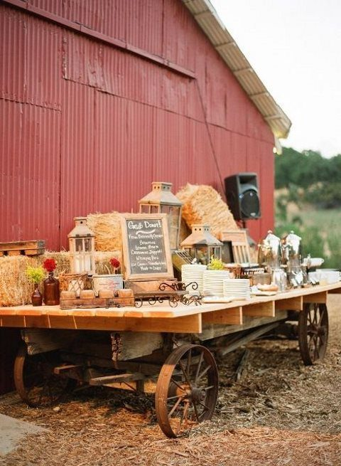 a table on wheels with hay, candle lanterns and chalkboard signs can be used to serve any food and drinks