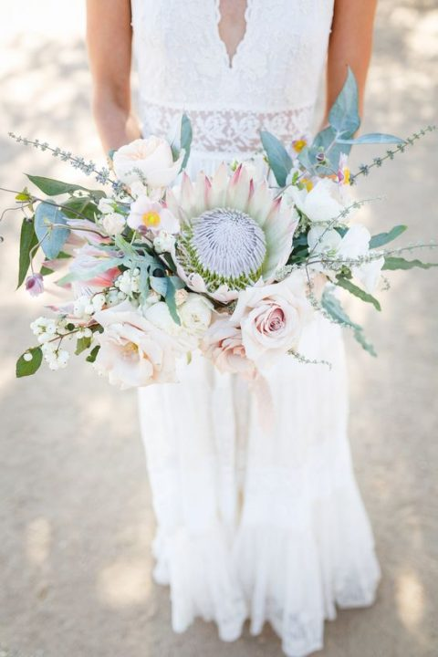 a textural wedding bouquet with blush blooms, a king protea, greenery and white berries