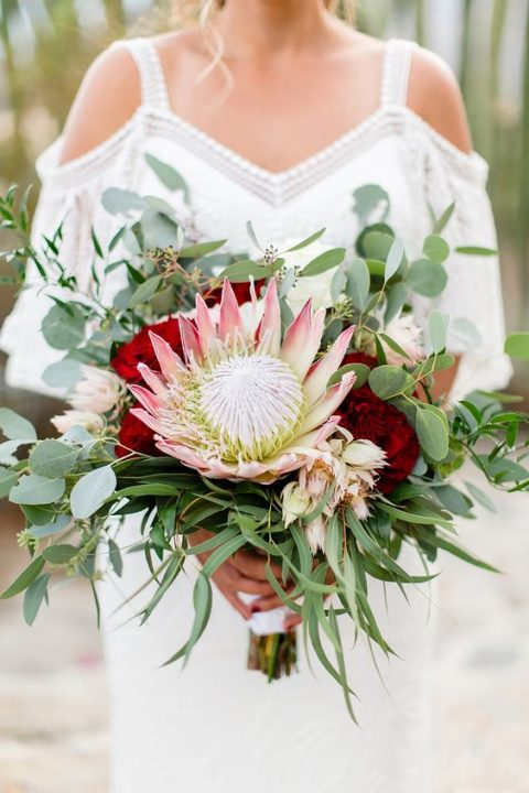 a textural wedding bouuet with a king protea, greenery, burgundy blooms