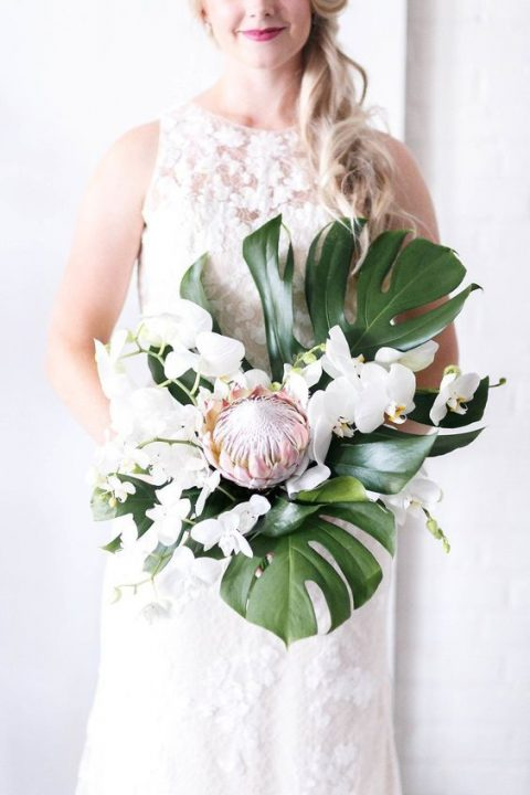 a tropical wedding bouquet with monstera leaves, white orchids and a single king protea