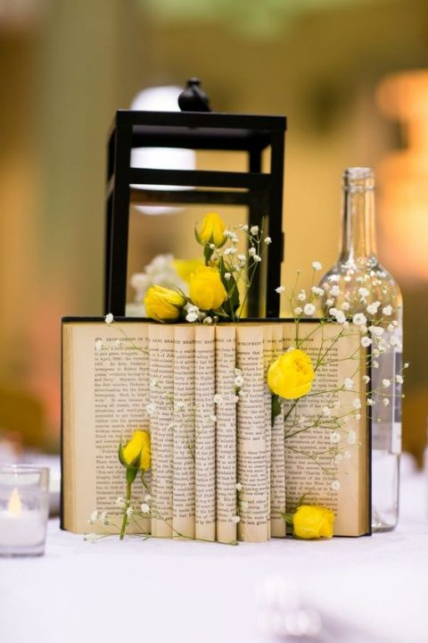 a vintage book with baby_s breath and yellow roses tucked in, a large metal lantern