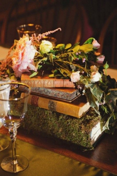 a wedding centerpiece with a moss covered book, soem vintage books, greenery and blooms placed on top