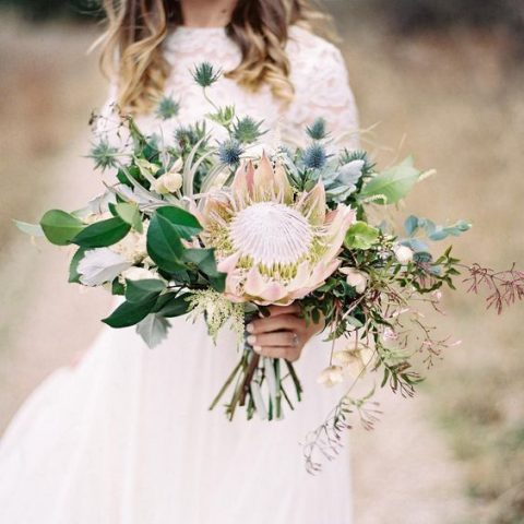 a wild wedding bouquet with a king protea, blue thistles, greenery