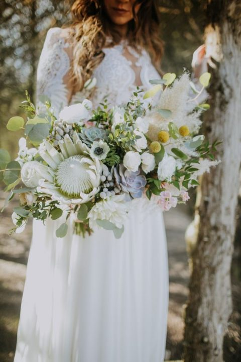an eclectic bridal bouquet with a king protea, white blooms, succulents, pampas grass and billy balls