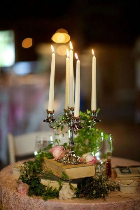an elegant and refined vintage centerpiece with books, greenery, blooms and a candelabra