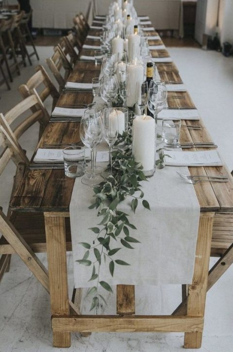 an elegant rustic tablescape with an uncovered table a linen runner, greenery, pillar candles and white menus