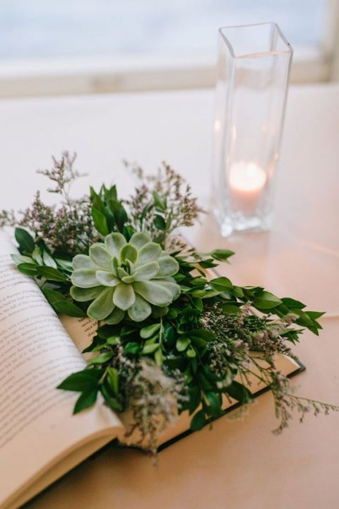 an opened book with lush greenery, blooms and a large succulent for a fresh look