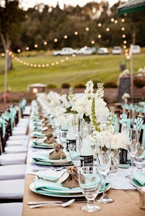 an outdoor rustic tablescape done in mint and with burlap, with white blooms and candles