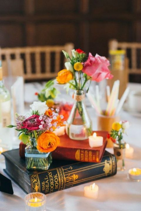 books, candles and mini vases with just some blooms in bold colors