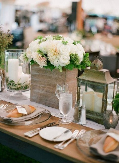 candle lanterns, a plywood planter with lush neutral blooms, sheer chargers and silver cutlery