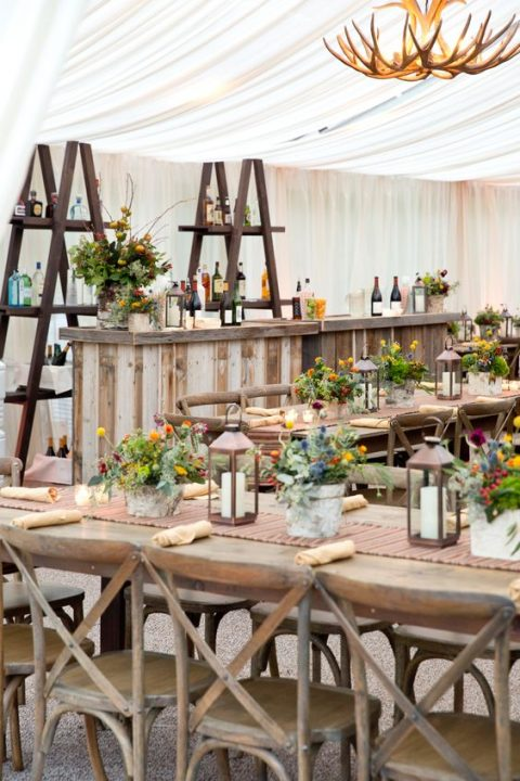candle lanterns and colorful potted blooms, pallet and weathered wood for rehearsal dinner decor with a rustic feel