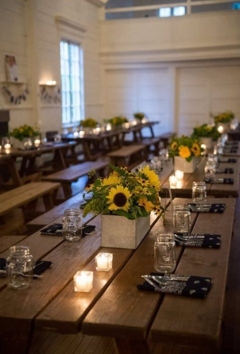 simple rustic tablescapes with uncovered tables, sunflower centerpieces, candles, dark napkins