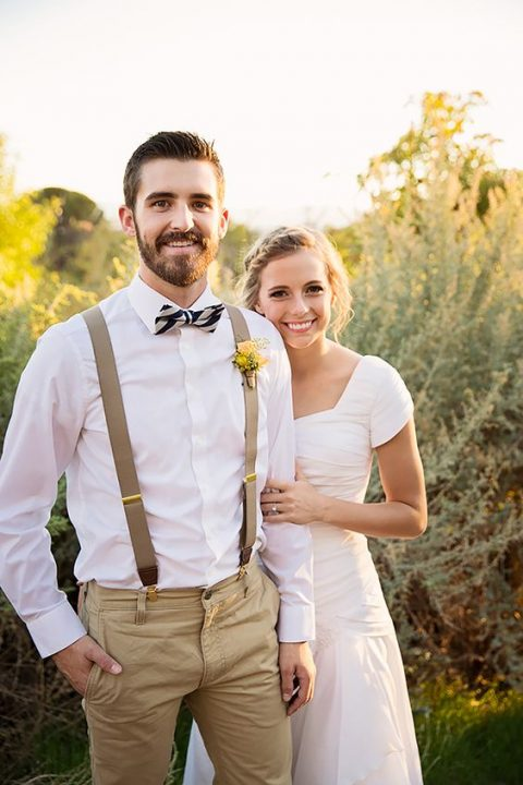tan pants and suspenders, a striped bow tie and a white button up