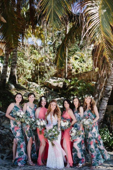 tropical beach bridesmaids_ dresses with a bold leaf and flower print and side slits and coral ones for the maids of honor