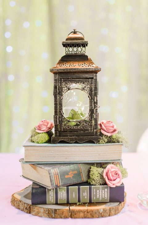 unique wedding centerpiece with a wood slice, moss, a stack of books, pink roses and a wooden candle lantern with LEDs inside