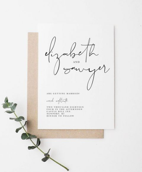 a chic modern wedding invitation in black and white with calligraphy and a kraft paper envelope