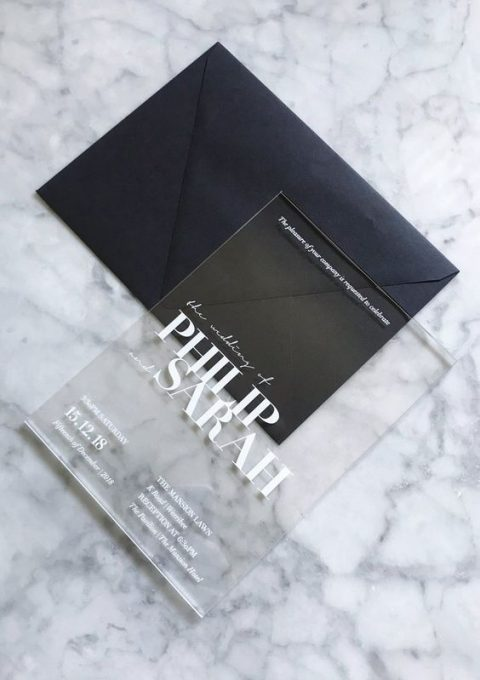 a clear acrylic wedding invite with white letters and a black envelope