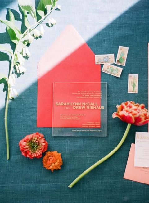 a modern acrylic wedding invitation with gold letters in a red envelope