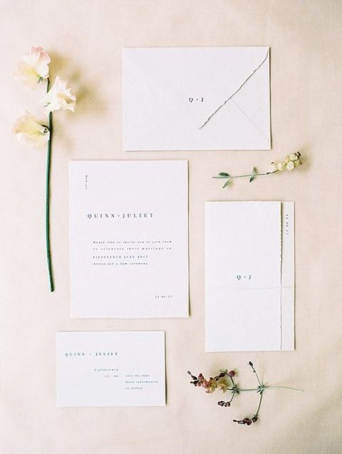an ethereal minimalist wedding invitation suite in white, with black lettering and a raw hem