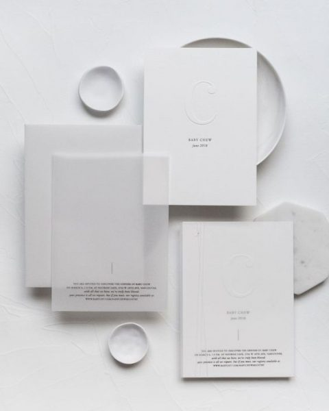 an ethereal wedding invitation suite in white with black letters and letterpressing
