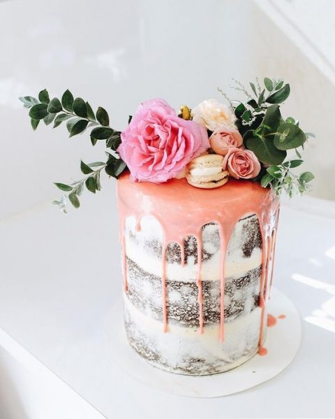 a chocolate naked wedding cake with pink drip, vanilla macarons, fresh blooms and foliage