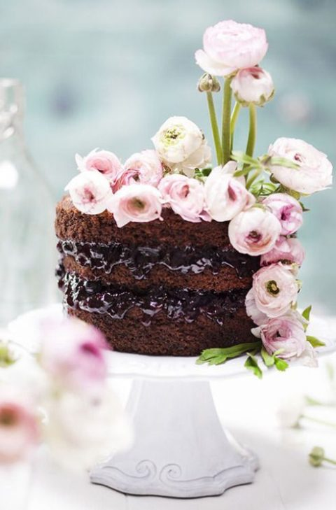 a naked chocolate wedding cake topped with pink ranunculus