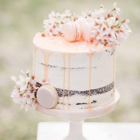 a naked spring wedding cake with blush dripping, macarons and cherry blossom