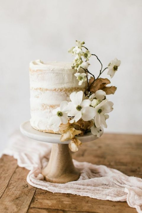 a naked wedding cake topped with dogwood blooms