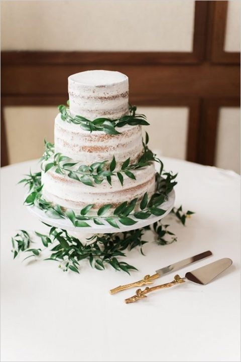 a naked wedding cake topped with fresh greenery