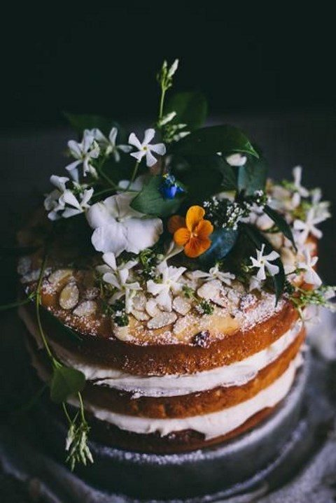 a naked wedding cake topped with wildflowers, greenery and almonds