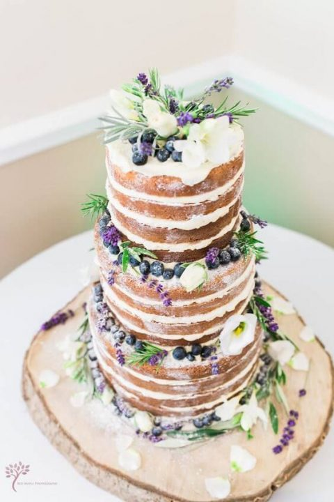 a naked wedding cake with berries, greenery and flowers on top