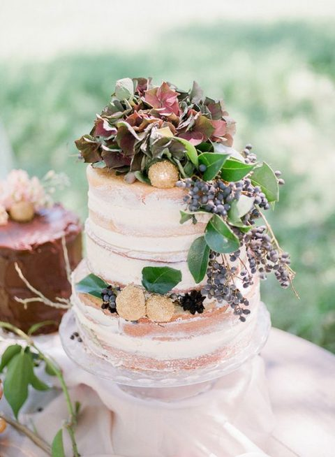 a naked wedding cake with berries, greenery and sugared fruit