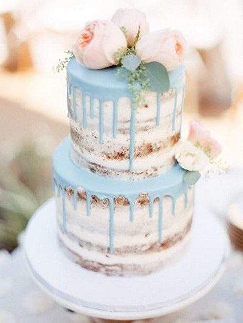a naked wedding cake with blue dripping and blush blooms