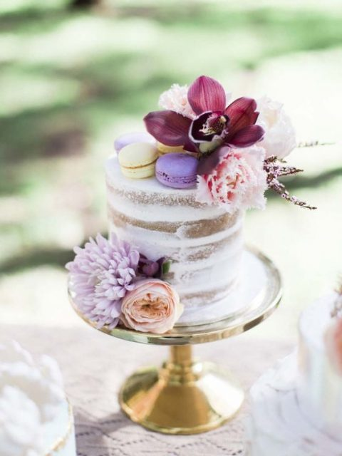 a naked wedding cake with blush blooms and a purple orchid plus colorful macaros on top