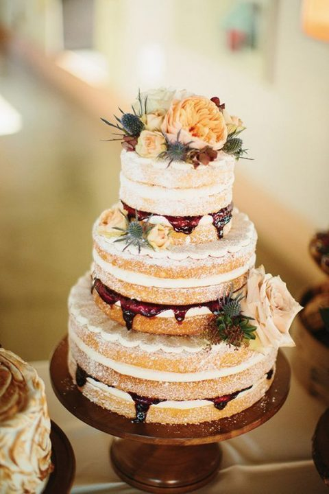 a naked wedding cake with thistles, yellow roses and other blooms on top