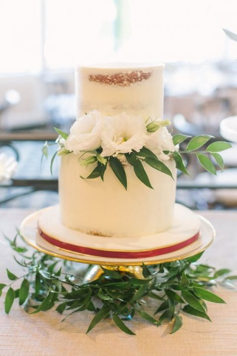 a semi-naked wedding cake with white blooms on top