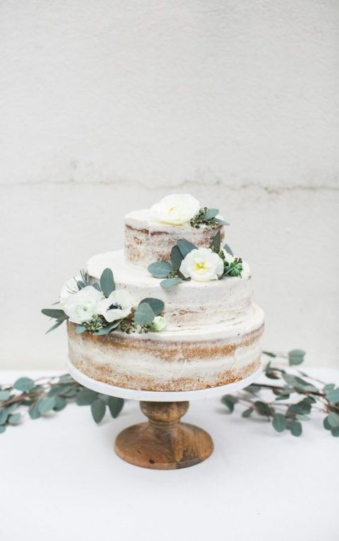 a three-tiered naked wedding cake decorated with white flowers and greenery
