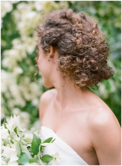 a braided low updo with natural curls is a chic way to make a statement