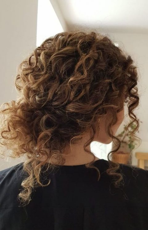 a curly messy low bun with bangs always works