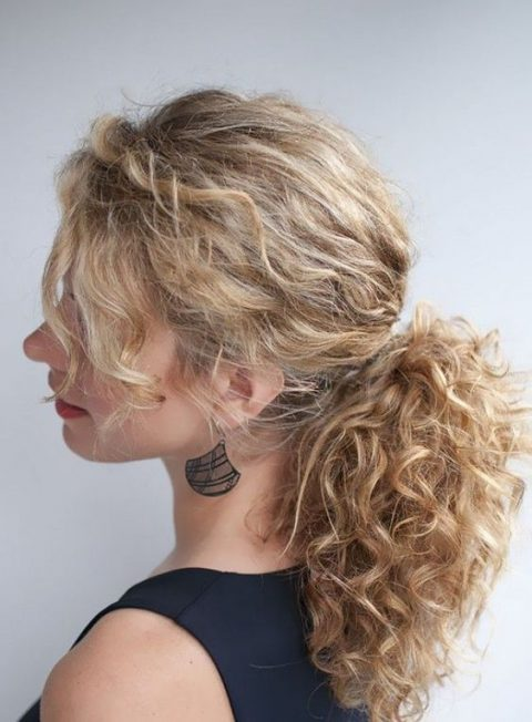 a messy low ponytail with bangs is a chic idea to rock for a modern wedding